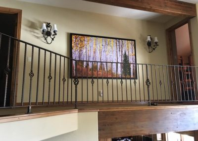 Artwork installed behind a bannister on a second story hallway between two lights
