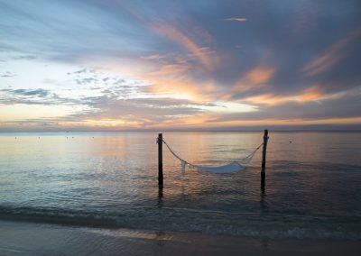 Hammock in the water on the beach with beautiful cloudy sky