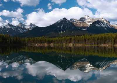Mountain and cloudy sky reflecting off of water