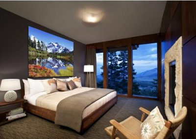 Large mountain and forest artwork installed over bed