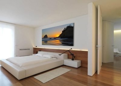 Large beach sunset artwork installed over bed