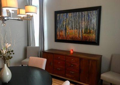 Framed woods artwork installed over table