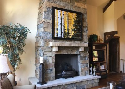 Mounted painting over stone fireplace
