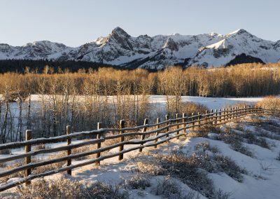 Snowy wooden fence with mountain range